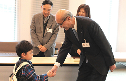 Chairman Miyamoto shakes hands with a small boy.