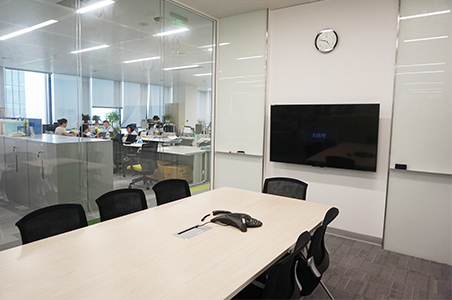 A sound-insulated meeting room in the center of the office. A glass partition was used to allow external lighting in, creating a sense of spaciousness.